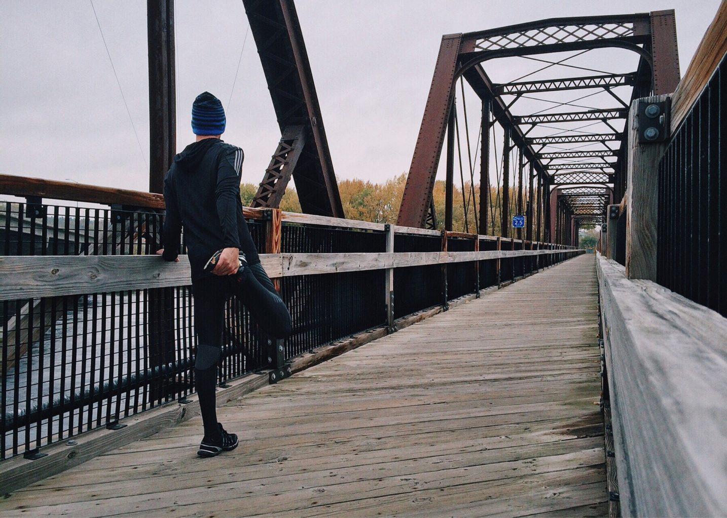 橋の上で準備体操をする、ニット帽着用の男性ランナー